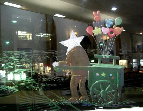 めぐり・ウインドー・ギャラリー第10弾は画家 はせがわいさおさんの<さぁ!みんな きっとパスする風船を届けに行こうよ>(2011年8月19日〜8月31日)